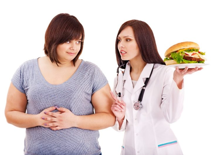 Overweight woman with hamburger and doctor.